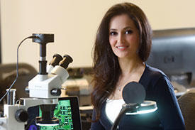 Sahar Mazloom at desk with microscope and computer.