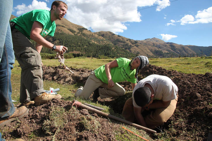 Three students digging a hole in a big open field with mountains in the background.